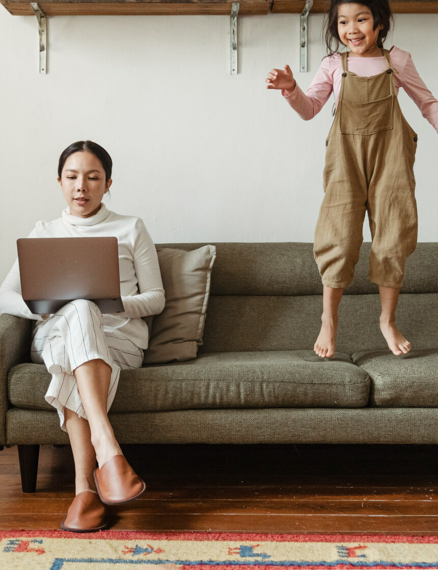 woman sitting on couch with laptop and young girl jumping