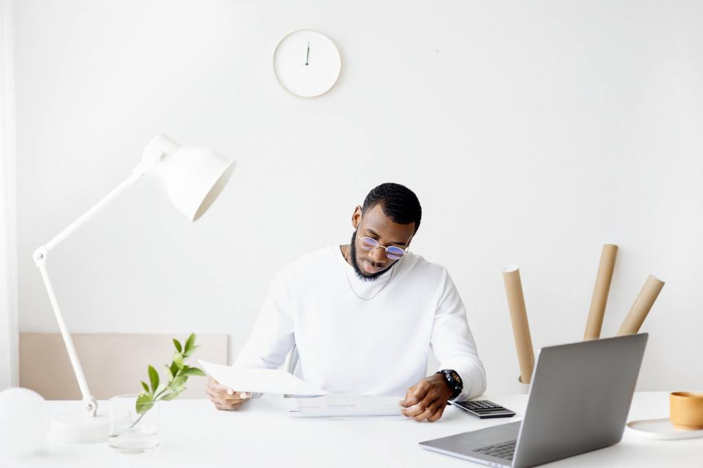 man budgeting at desk with phone calculator