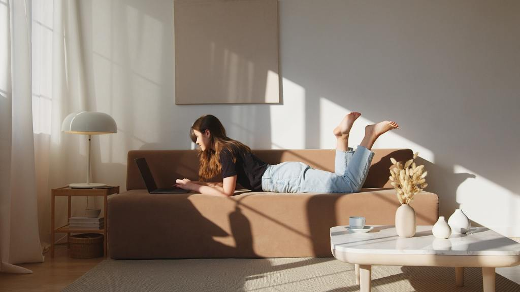 woman lying on couch working