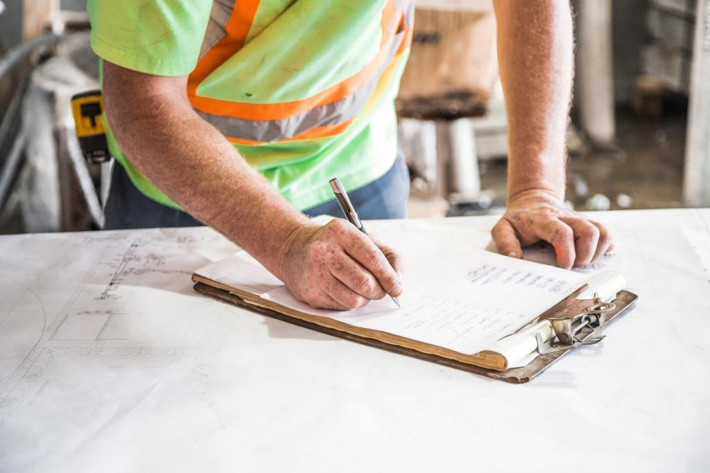 construction worker planning renovation on clipboard