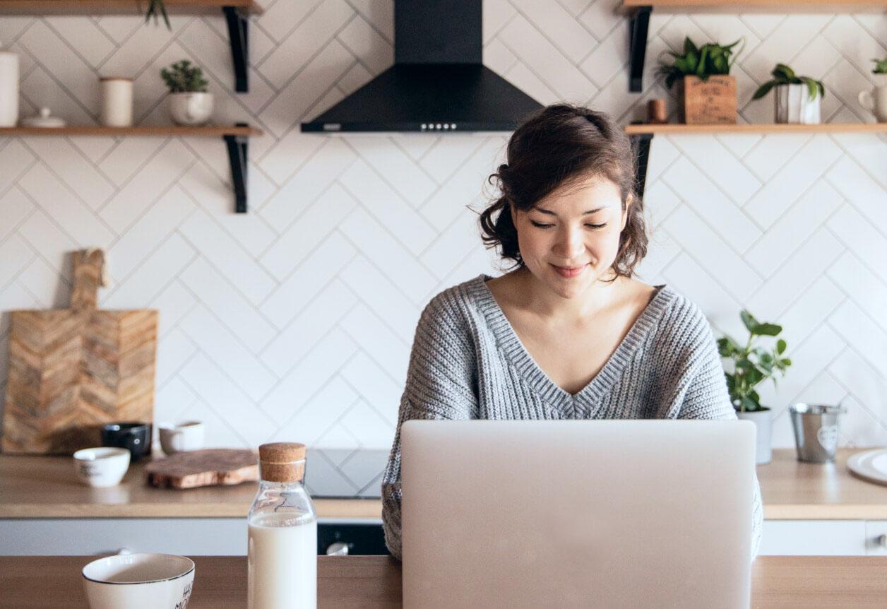 femme qui utilise un ordinateur portable dans la cuisine