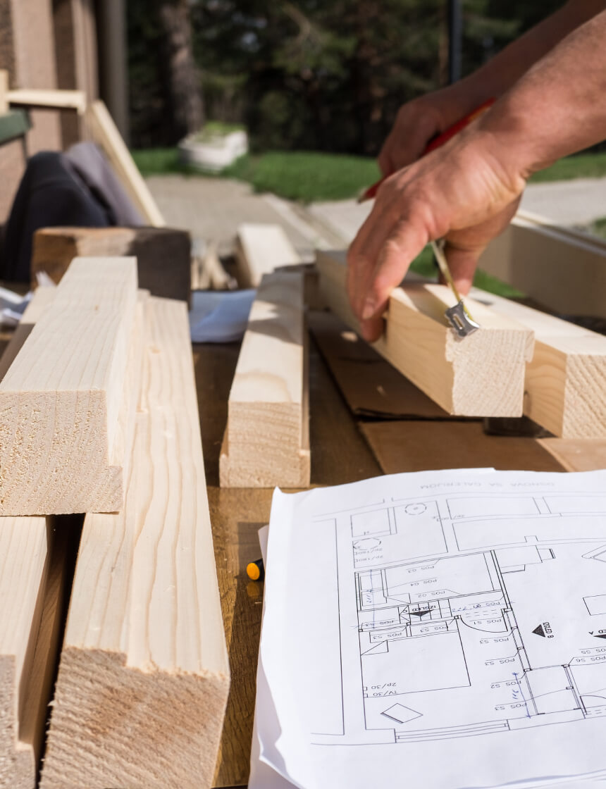entrepreneur prenant les mesures d'une pièce de bois