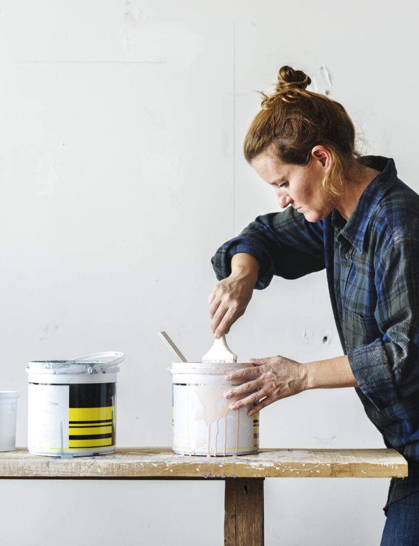 Jeune entrepreneure qui brasse de la peinture dans un sceau